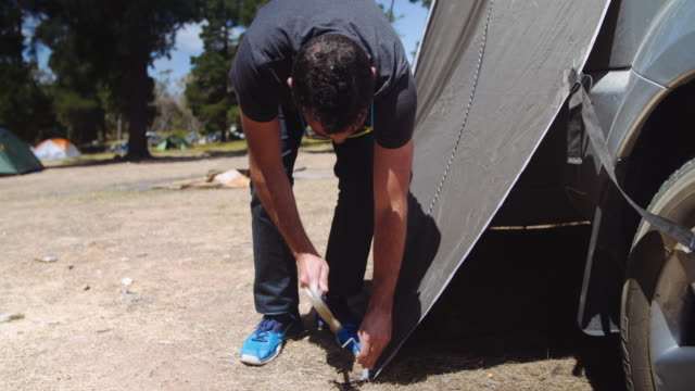 A day in the life of a climbing couple: man setting up the tent