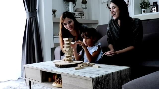Día en la vida de una familia: lindo asiatico jugando con bloques. Formato de alta definición.