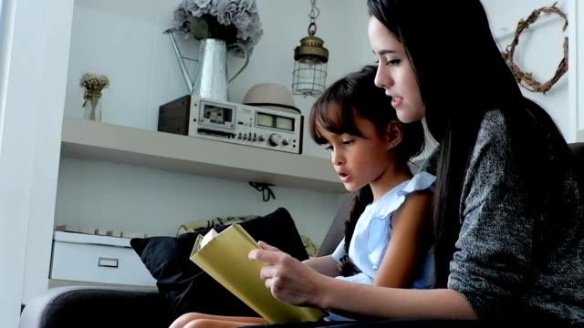 Journée dans la vie d'une famille: mère et fille lecture livre. Format de HD.