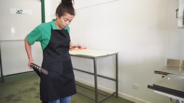 A day in the life of a female butcher: woman cutting meat