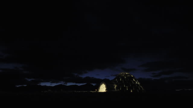 MS T/L Day last light fading away over a mountain vista with an igloo on ground,Candle light remains on in Igloo and switches off towards end With cloud movement / Bohinj, Triglav, Slovenia