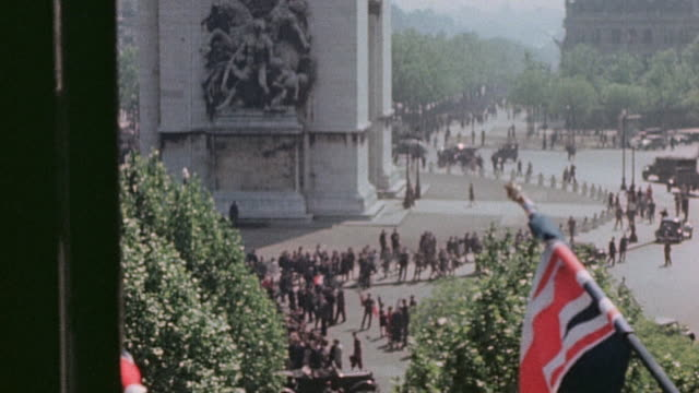 day procession circling the arc de triomphe and onlooker looking out a window and waving / paris france - ve day stock-videos und b-roll-filmmaterial