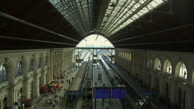day time-establishing interior shot of main train station with people walking around.  slow zoom - budapest stock videos & royalty-free footage