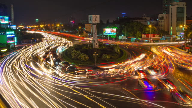 vídeos de stock e filmes b-roll de day timelapse of traffic moving around roundabout, ho chi minh city (saigon), vietnam - time lapse de trânsito