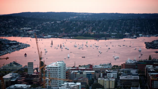A day to dusk aerial time lapse of dozens of small sailboats on Lake Union (in Seattle, Washington), participating in the weekly Duck Dodge sailing event.
