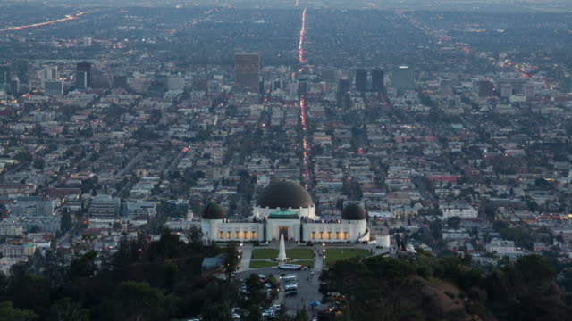 day to dusk view of griffith park observatory over a sprawling los angeles - griffith observatory stock videos & royalty-free footage