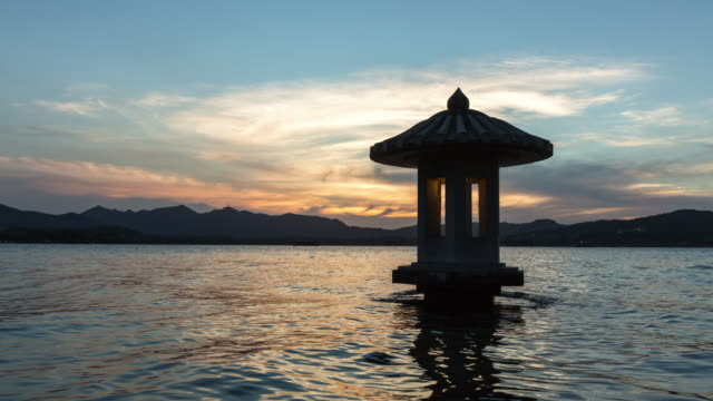 day to night 4k time-lapse:an illuminated stone lantern on the west lake against sunset,hangzhou,china - sunset to night time lapse stock videos & royalty-free footage