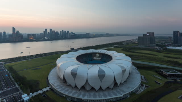 day to night 4k time-lapse:hangzhou olympic sports center against the qiantang river at dusk,hangzhou,china - オリンピックスタジアム点の映像素材/bロール