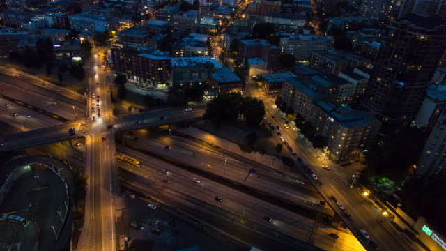 A day to night aerial time lapse of traffic on several roads in Seattle, Washington, including Interstate 5 and four surface street overpasses, featuring glimpses of the Capitol Hill neighborhood and the Convention Center bus depot.