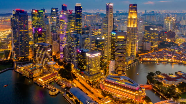 vídeos de stock e filmes b-roll de day to night aerial view dronelapse or hyperlapse of financial central business district building of singapore city - arranha céu