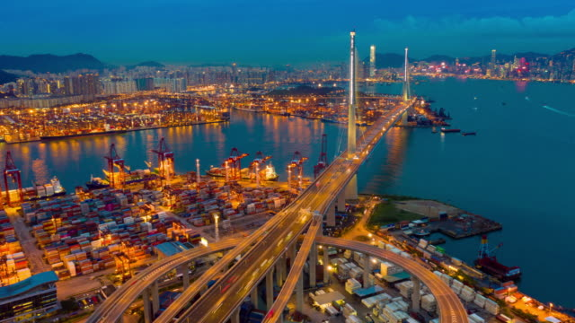 vídeos de stock e filmes b-roll de day to night aerial view hyperlapse or timelapse of hong kong kwai tsing container terminals and stonecutters bridge at dusk - navio cargueiro
