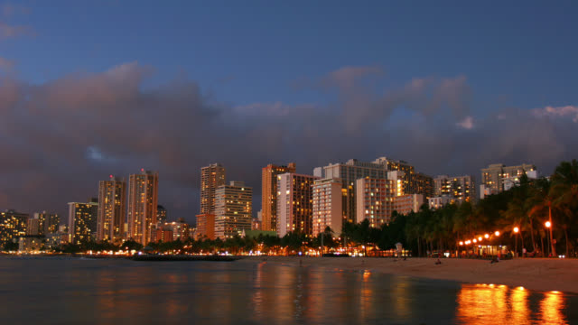time lapse wide shot day to night clouds over waterfront hotels in waikiki - insel oahu stock-videos und b-roll-filmmaterial