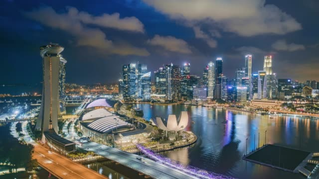 vidéos et rushes de day to night hyper lapse of the singapore skyline and financial district at dusk, showing marina bay - singapour