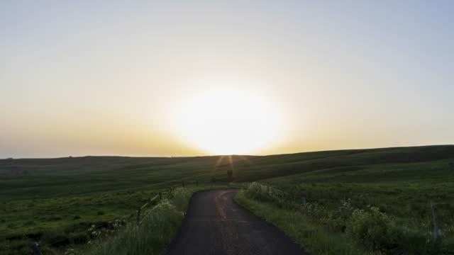 vidéos et rushes de pov day to night hyperlapse t/l driving downhill on road along meadows - scène tranquille