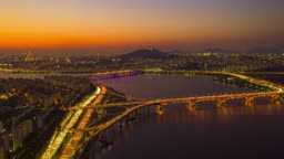 Day to night Hyperlapse or Dronelapse Aerial view of Seoul downtown city skyline with light trails on expressway and bridge cross over Han river at night in Seoul city, South Korea.