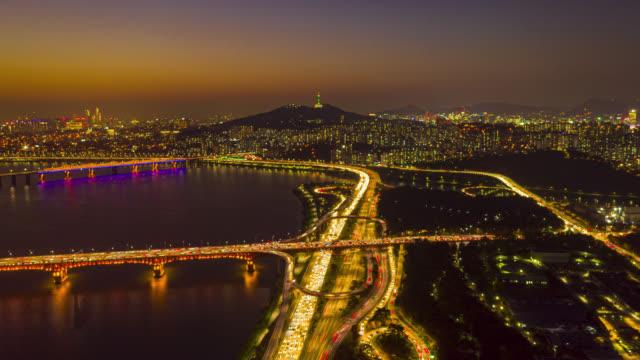 vídeos y material grabado en eventos de stock de día a la noche hyperlapse o dronelapse vista aérea del horizonte de la ciudad de seúl con senderos de luz en la autopista y puente cruzan sobre el río han por la noche en la ciudad de seúl, corea del sur. - seúl