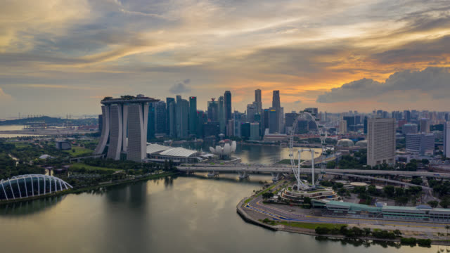 day to night hyperlapse or dronelapse scene of singapore business district downtown at sunset - torre struttura edile video stock e b–roll
