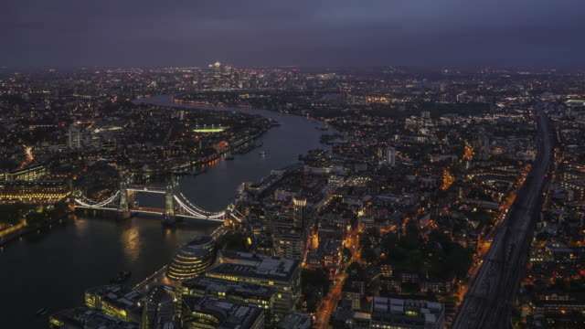 Day to night, looking east along the River Thames with Tower Bridge and Canary Wharf in the distance.