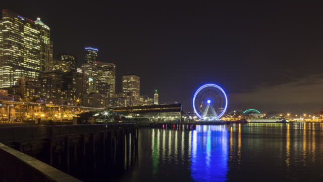 A day to night panning time lapse of the Seattle waterfront, featuring views of Harbor Island, CentryLink Field, the Great Wheel, Smith Tower, and Columbia Tower.