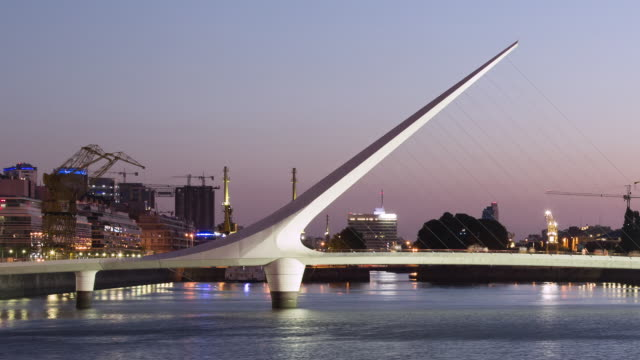 TL, LS Day to night, pedestrains cross Puente de la Mujer in Puerto Madero / Buenos Aires, Argentina