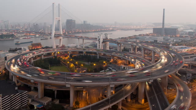 vídeos de stock, filmes e b-roll de tl, ws, ha day to night rush hour traffic spirals around nanpu bridge / shanghai, china - time lapse de trânsito