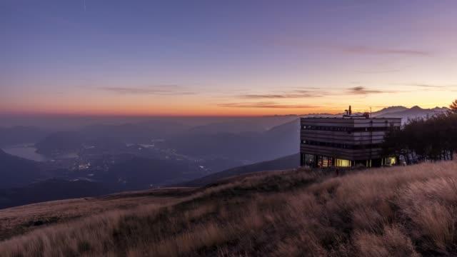 tag für nacht schuss einer berghütte über stadt und see - zeitraffer tag bis nacht stock-videos und b-roll-filmmaterial