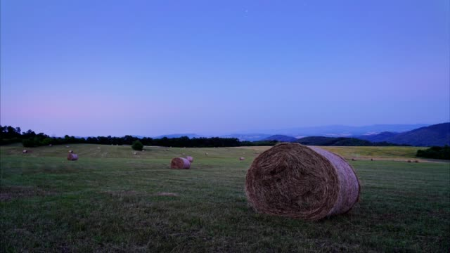 pov, day to night time lapse of a moody sky evening over the bales of hay in the field. - haystack stock videos & royalty-free footage