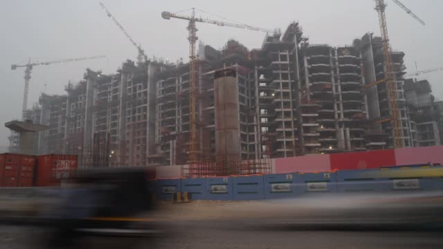 Day to night time lapse of busy traffic on a orad in front of a metro and building construction site in Delhi NCR