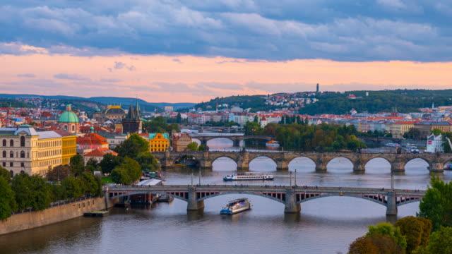 vídeos de stock, filmes e b-roll de dia a noite time lapse da ponte charles e do rio vltava que flui através de praga, república checa - praga