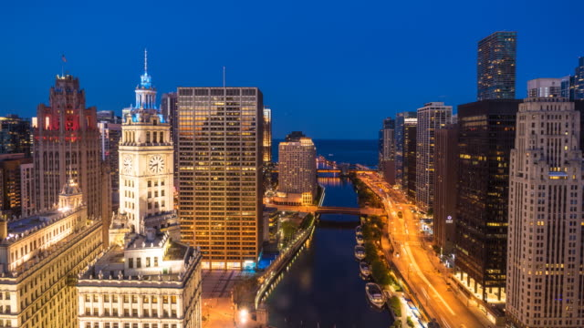 Day to night time lapse of Chicago cityscape and river towards Lake Michigan, with traffic on bridges and Wacker Drive