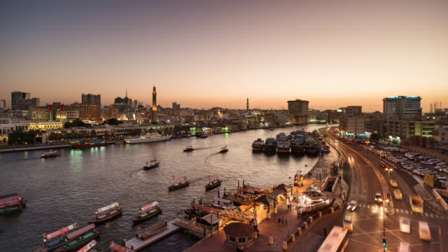 tl/ day to night time lapse of dubai creek and spice market, at sunset with passing cargo boats and traffic. - martin luther: his life and time stock videos & royalty-free footage