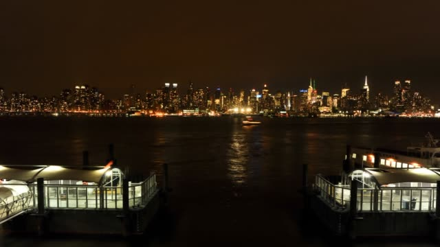 Day to night time lapse of ferries sailing with the skyline in the foreground in New York NY US on February 4th Wide shot of a ferry sailing by rocks...