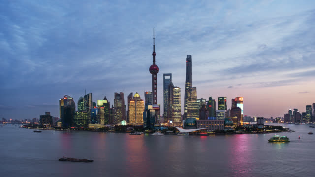 tl/ day to night time lapse of the shanghai skyline, cargo ships on the pudong river passing by the financial district - martin luther: his life and time stock videos & royalty-free footage