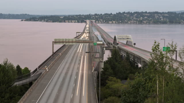 stockvideo's en b-roll-footage met day to night time lapse of traffic crossing the 520 floating bridges connecting seattle to the eastern suburbs of bellevue and redmond on a gray, overcast day - staat washington