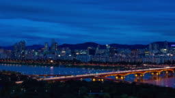 Day to night time lapse shot of Seoul cityscape with Han River and traffic on expressway, South Korea
