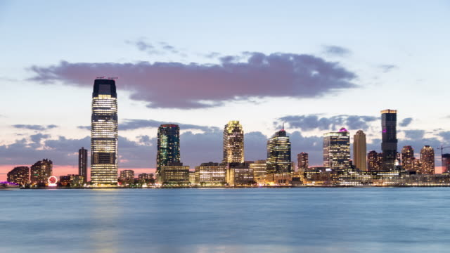 A day to night time lapse taken from the Battery Park City Esplanade of the Hudson River with Exchange Place in Jersey City, NJ, in the background featuring Colgate Clock