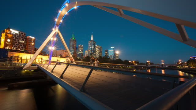 a day to night time lapse view of melbourne from the southbank pedestrian bridge at dusk. - david ewing stock-videos und b-roll-filmmaterial