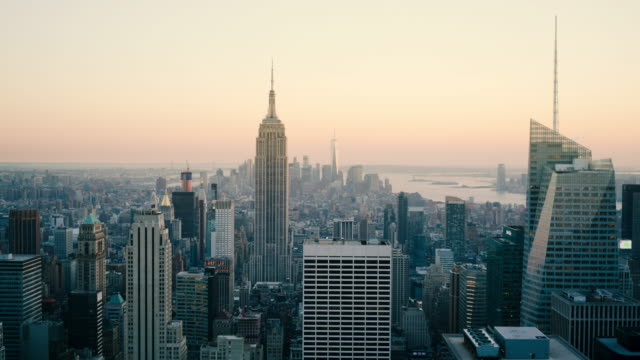 day to night time-lapse aerial view of empire state building and freedom tower, new york, usa - empire state building stock-videos und b-roll-filmmaterial