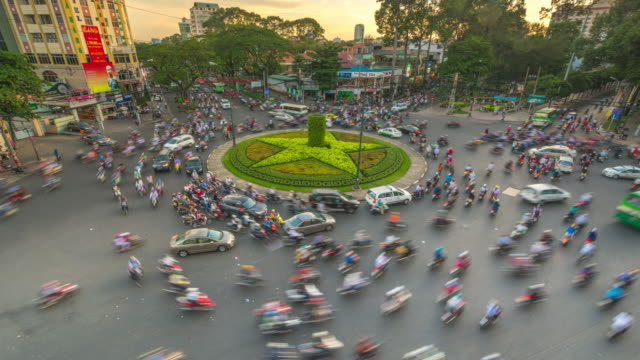 vídeos de stock e filmes b-roll de day to night timelapse of busy motorbike traffic at six way junction in ho chi minh city (saigon), vietnam - 2013