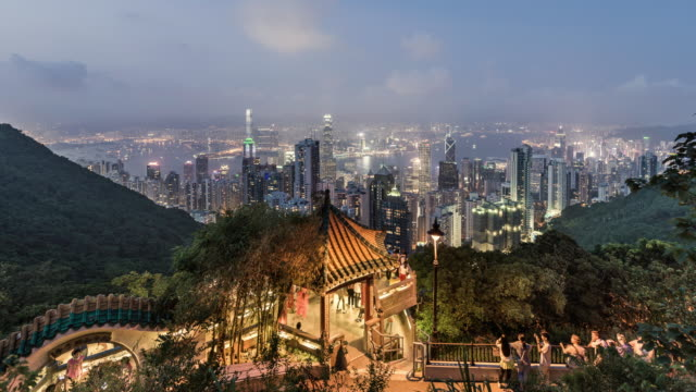 day to night timelapse of people in front of hong kong skyline - victoria peak stock videos & royalty-free footage