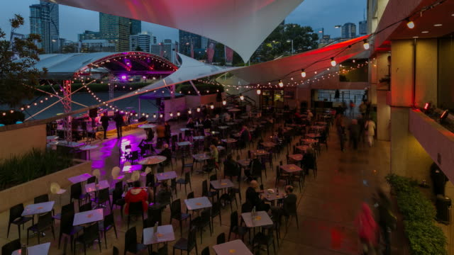 Day to night time-lapse of people sitting for a public concert in Brisbane, Australia