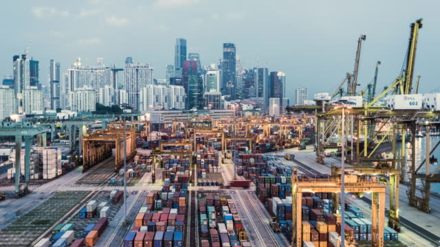 T/L day to night timelapse of Singapore's cargo and container port infront of the financial district and skyline