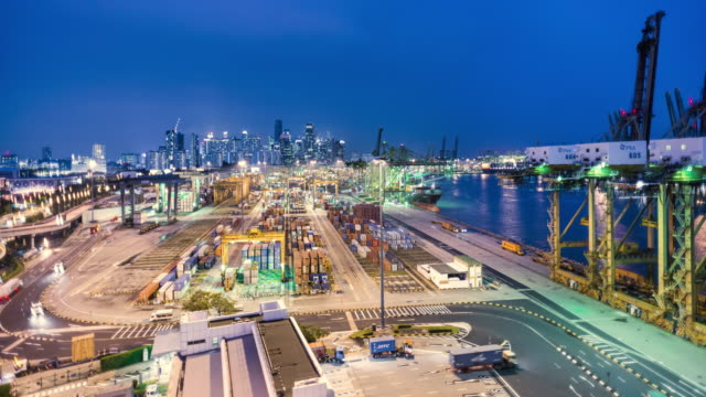 T/L day to night timelapse of Singapore's cargo container port infront of the financial district and skyline