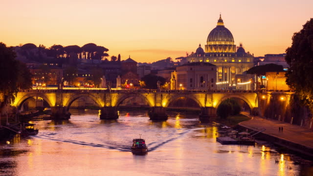 Day to night timelapse of the dome of Saint Peters Basilica and Vatican City. Sant'Angelo Bridge over the Tiber River. Rome, Italy