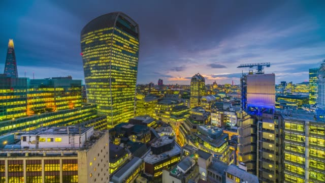 day to night time-lapse of the sunset over city of london skyline with skyscrapers illuminated at twilight. - shard london bridge stock videos & royalty-free footage