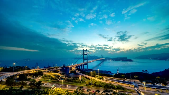 T/L Day to night timelapse of Tsing Ma Bridge in Hong Kong with busy road and sea traffics with 2 compositions
