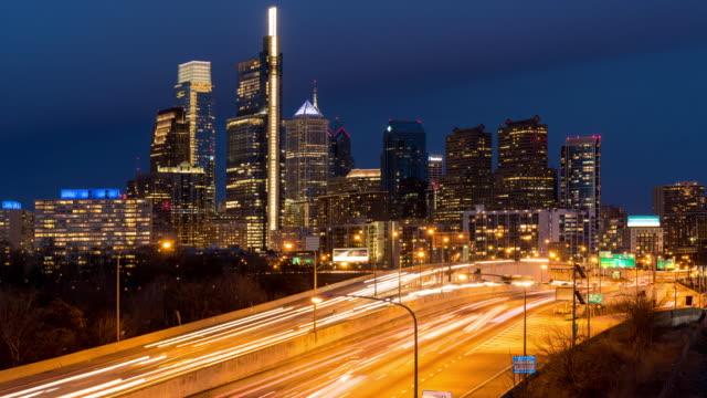 昼から夜のタイムラプス:フィラデルフィアハイウェイとpa usaのスカイライン超高層ビルの街並み - センターシティ点の映像素材/bロール