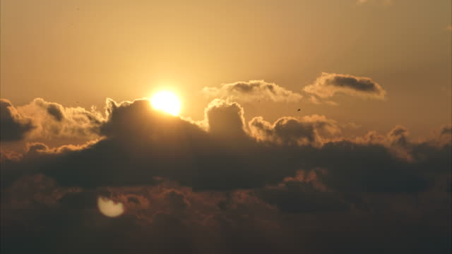 Day to night timelapse sequence of close-up sun setting between clouds