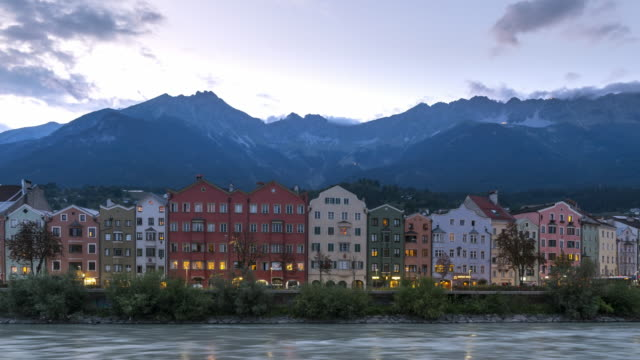 day to night timelapse view by looking at a view of cityscape view of multi-color austrian building with  nordkette mountain and hafelekarspitze-seegrube, one of alps of austria, glacier mountain range,  in the morning summer season, innsbruck austria - traditionally austrian stock videos & royalty-free footage