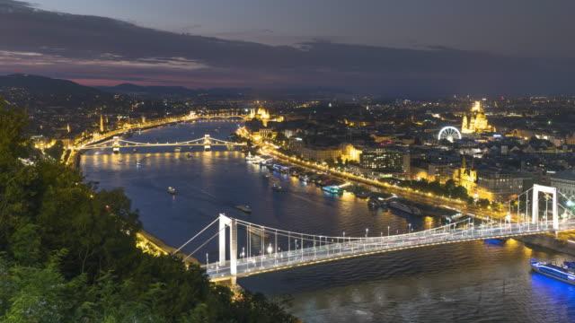 vidéos et rushes de du jour au soir tl: chain bridge avec cityscape de budapest autour du danube le soir de gellért hill - pont à chaînes pont suspendu